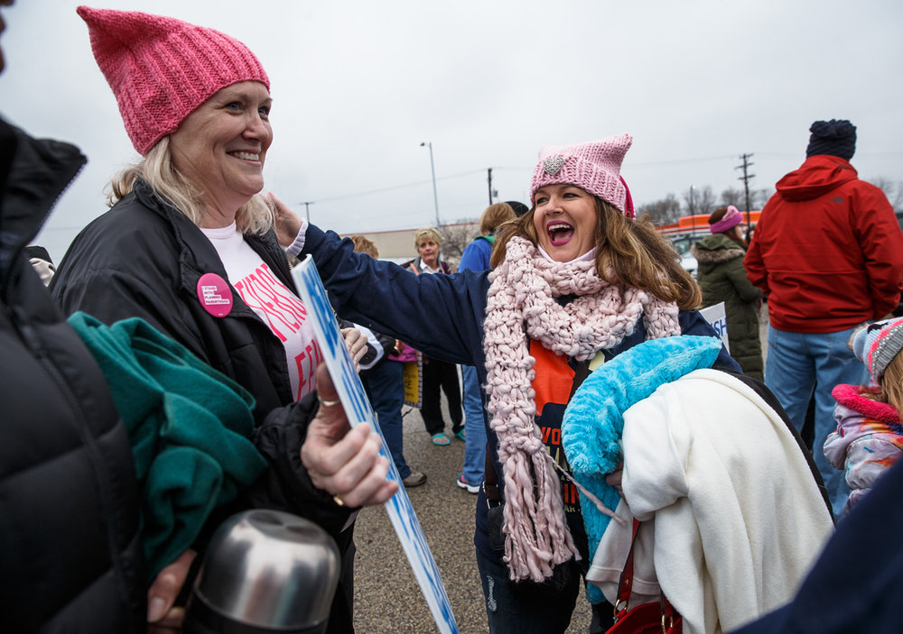 Lynie MacKenzie, center, laughs at the sign that Melanie Hoyle, left, prepared to march with as a group from central Illinois prepares to depart for Washington D.C. for the Women's March from the parking lot of JCPenny, Friday, Jan. 20, 2017, in Springfield, Ill. Justin L. Fowler/The State Journal-Register