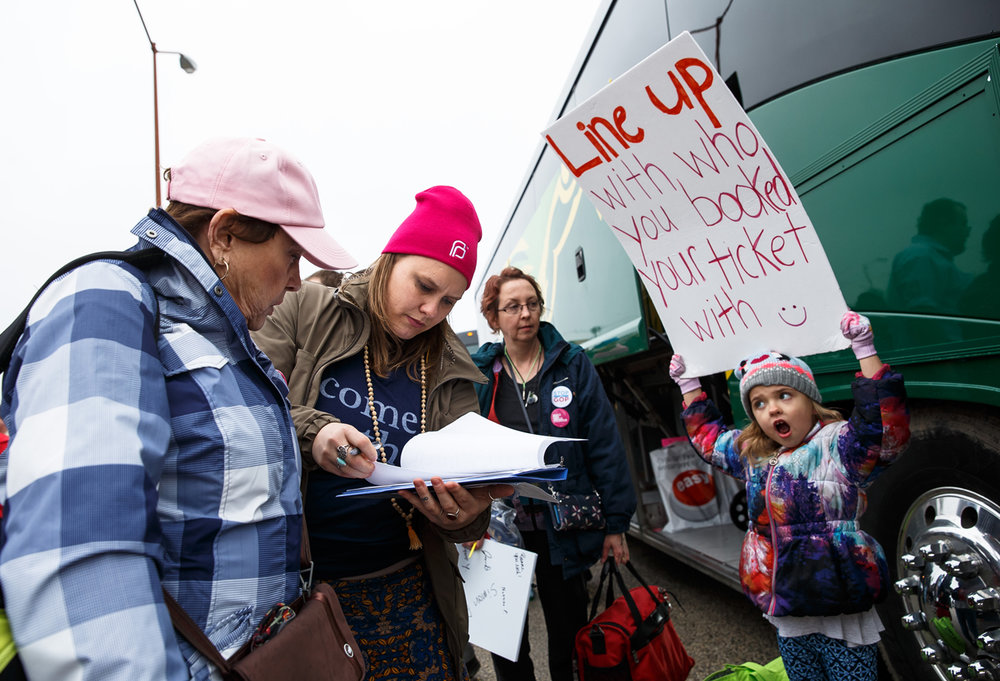 Ashley Eikenberry, center, checks in those loading on the bus with the help of her daughter, Anelia Eikenberry, 6, right, as those from around central Illinois prepare to depart for Washington D.C. for the Women's March from the parking lot of JCPenny, Friday, Jan. 20, 2017, in Springfield, Ill. Justin L. Fowler/The State Journal-Register