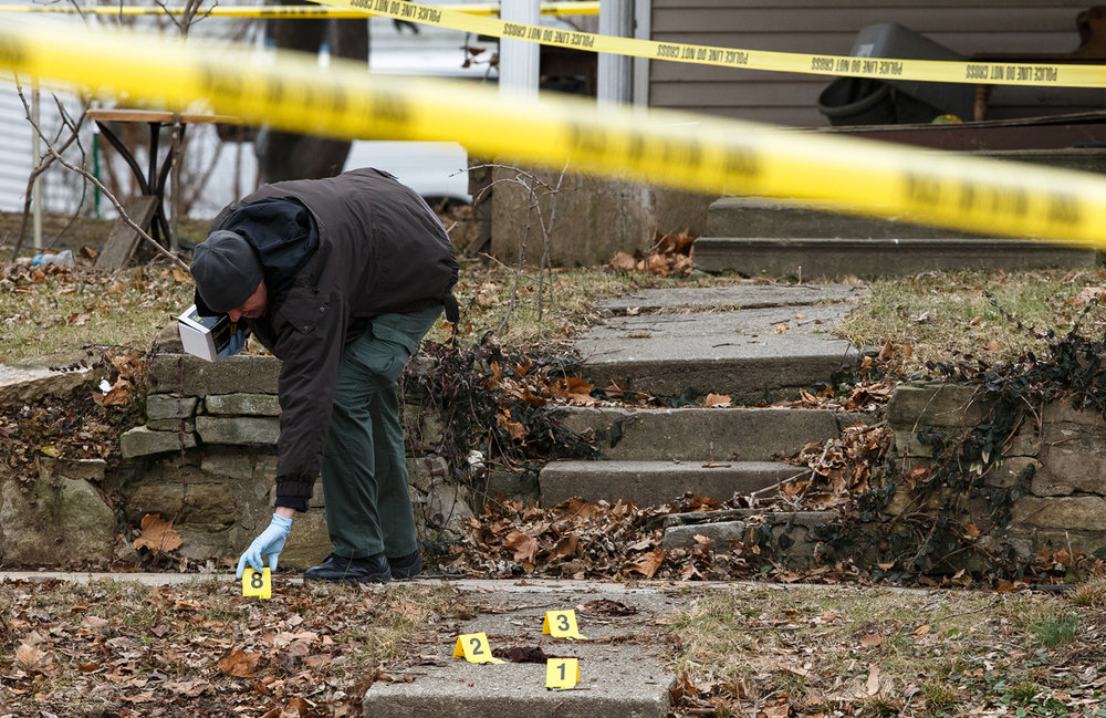 Crime scene investigators with the Illinois State Police place evidence markers along the sidewalk as they investigate the scene of an apparent shooting of a man involving a Springfield Police officer near Walnut and Carpenter streets, Monday, Jan. 23, 2017, in Springfield, Ill. Justin L. Fowler/The State Journal-Register
