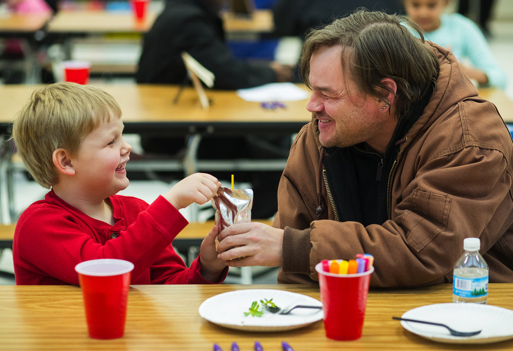 Liam Spain and his dad Christian laugh together during the Fathers are Fundamental event at  Enos Elementary School Thursday, Jan. 26, 2017. The family engagement event highlighted different ways that fathers are a key to the success of their children. After snacks and a presentation, guests helped their student create an after school schedule designed to prepare for the following school day. Ted Schurter/The State Journal-Register
