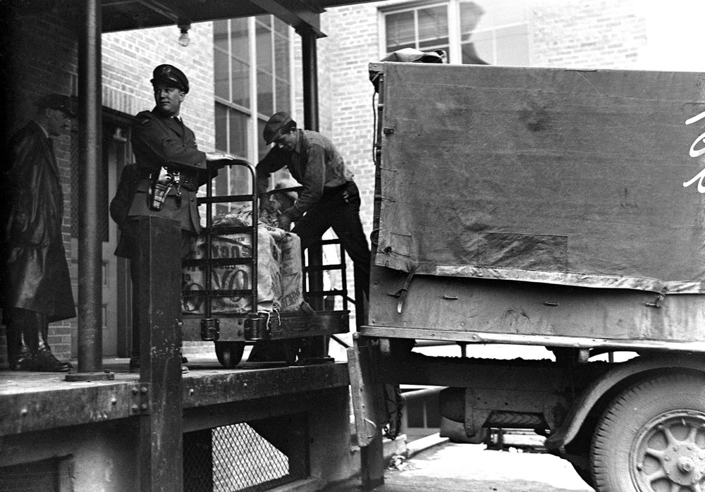 Sugar sacks loaded with gallon containers of alcohol being seized by Deputy Prohibition Administrator James A. Eaton, at loading dock of federal building. Illinois State Journal glass plate negative/Sangamon Valley Collection at Lincoln Library. All Rights Reserved, The State Journal-Register. pub. ISJ Feb 20, 1931, p. 12. C-98-601, neg #901