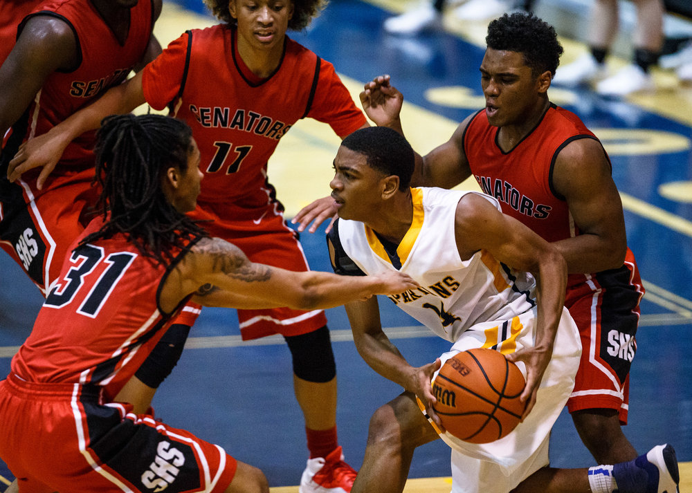 Southeast's Trevyon Williams (14) is surrounded by a trio of Springfield defenders in the second quarter at Herb Scheffler Gymnasium, Tuesday, Feb. 7, 2017, in Springfield, Ill. [Justin L. Fowler/The State Journal-Register]