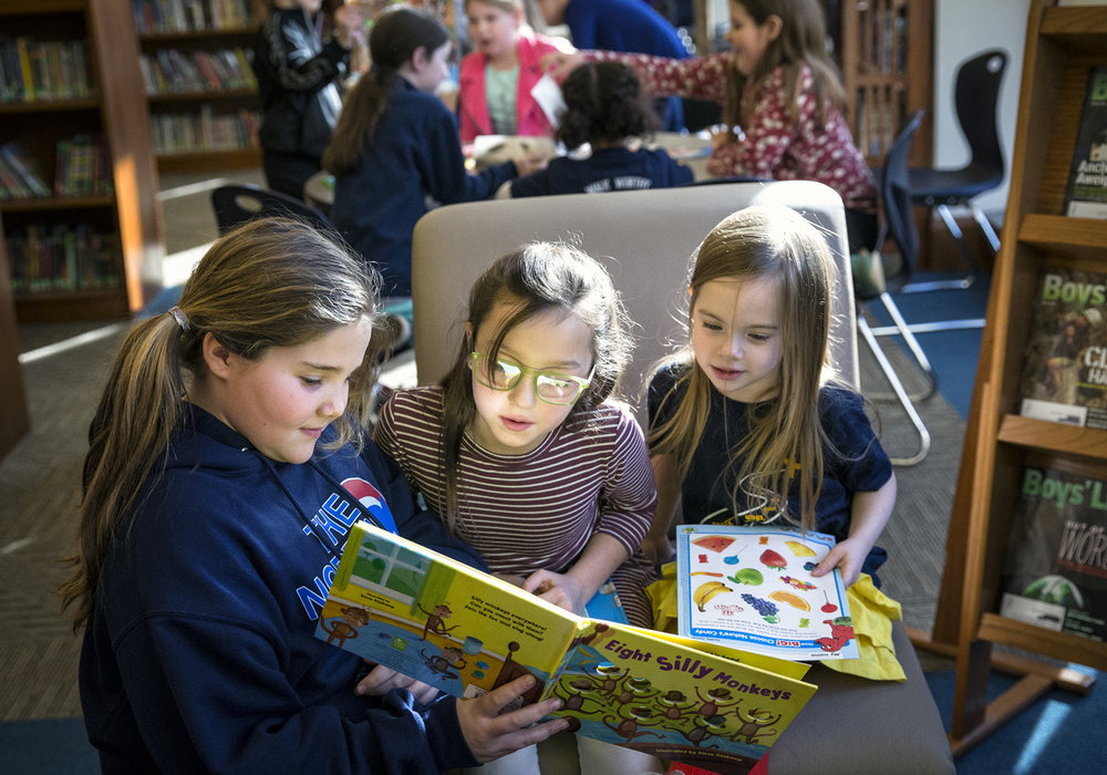 "Blessed Sacrament fourth graders Ava DeSalle, 10, left, and Laney Aleman, 9, center, read the book ""Eight Silly Monkeys"" to preschooler Hannigan Chambers, 5, right, during a Read-A-Thon at Blessed Sacrament School, Monday, Jan. 30, 2017, in Springfield, Ill. The Read-A-Thon was held to raise funds for the school's partner, St. TheresaÕs Center for Youth Development in Kaluri. Ghana, to purchase the necessary equipment to provide internet service. This would allow students from Blessed Sacrament to communicate with their peers in Ghana via the internet to share their lives and cultures with one another. Justin L. Fowler/The State Journal-Register"