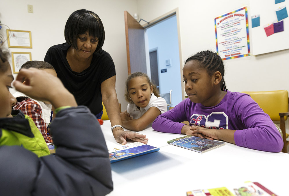 "Minnie Robinson, left, helps turn the pages as Ilanna Wiley, 11, center, and Jaeda Johnson, 9, right, help read the book ""Barney's Mother Goose Hunt"" to younger children in their group during the annual African American Read In at St. John A.M.E. Church, Monday, Feb. 6, 2017, in Springfield, Ill. The program is part of Black History Month and encourages the youth to read more and for the adults to discuss works by African American authors. [Justin L. Fowler/The State Journal-Register]"