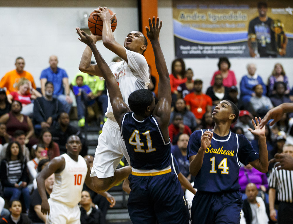 Lanphier's Cardell McGee (2) draws the foul as he goes up for a basket against Southeast's Robert Hayes (41) in the fourth quarter at Lober Nika Gymnasium, Tuesday, Feb. 21, 2017, in Springfield, Ill. McGee led the Lions in scoring with 26 points in their 65-50 victory over Southeast. [Justin L. Fowler/The State Journal-Register]