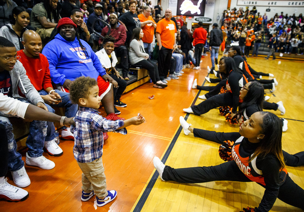 Jerald Maxwell, 2, offers members of the Lanphier Poms a Twizzler as they perform their opening routine to the school song as the Lions prepare to take on Southeast at Lober Nika Gymnasium, Tuesday, Feb. 21, 2017, in Springfield, Ill. [Justin L. Fowler/The State Journal-Register]