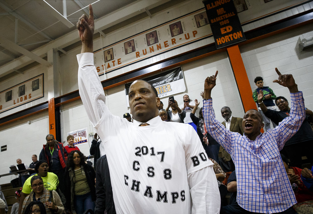 Lanphier boys basketball head coach Blake Turner puts on a t-shirt declaring the Lions the CS8 Champions after they defeated Southeast 65-50 at Lober Nika Gymnasium, Tuesday, Feb. 21, 2017, in Springfield, Ill. [Justin L. Fowler/The State Journal-Register]