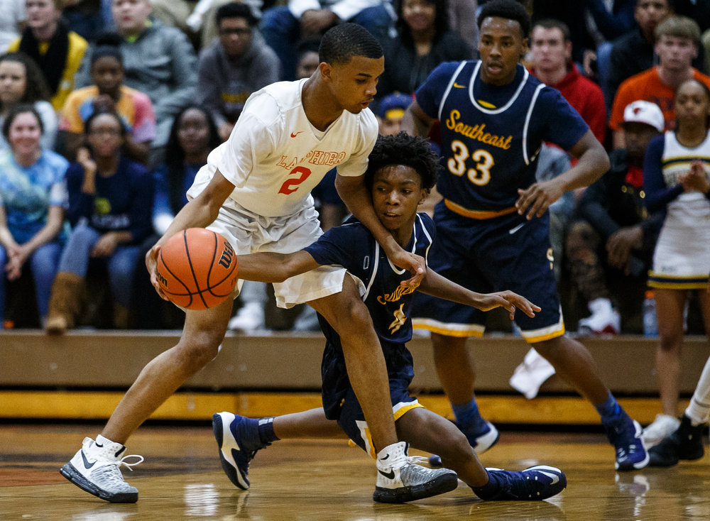 Southeast's Terrion Murdix (4) tries to knock the ball away from Lanphier's Cardell McGee (2) in the first quarter at Lober Nika Gymnasium, Tuesday, Feb. 21, 2017, in Springfield, Ill. [Justin L. Fowler/The State Journal-Register]