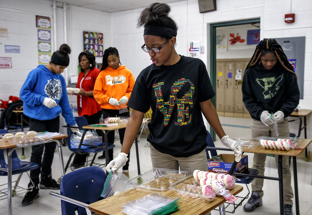 "Raya Johnson, 13, sings along to a song as she packages cookies in preparation for their delivery as ""Cookie Grams"" along with her fellow student volunteers at Franklin Middle School, Tuesday, Feb. 14, 2017, in Springfield, Ill. Around 415 ""Cookie Grams"" were purchased by students at the school to be delivered to their friends and teachers and the proceeds will go towards the Springfield and Central Illinois African American History Museum to celebrate Black History Month. [Justin L. Fowler/The State Journal-Register]"