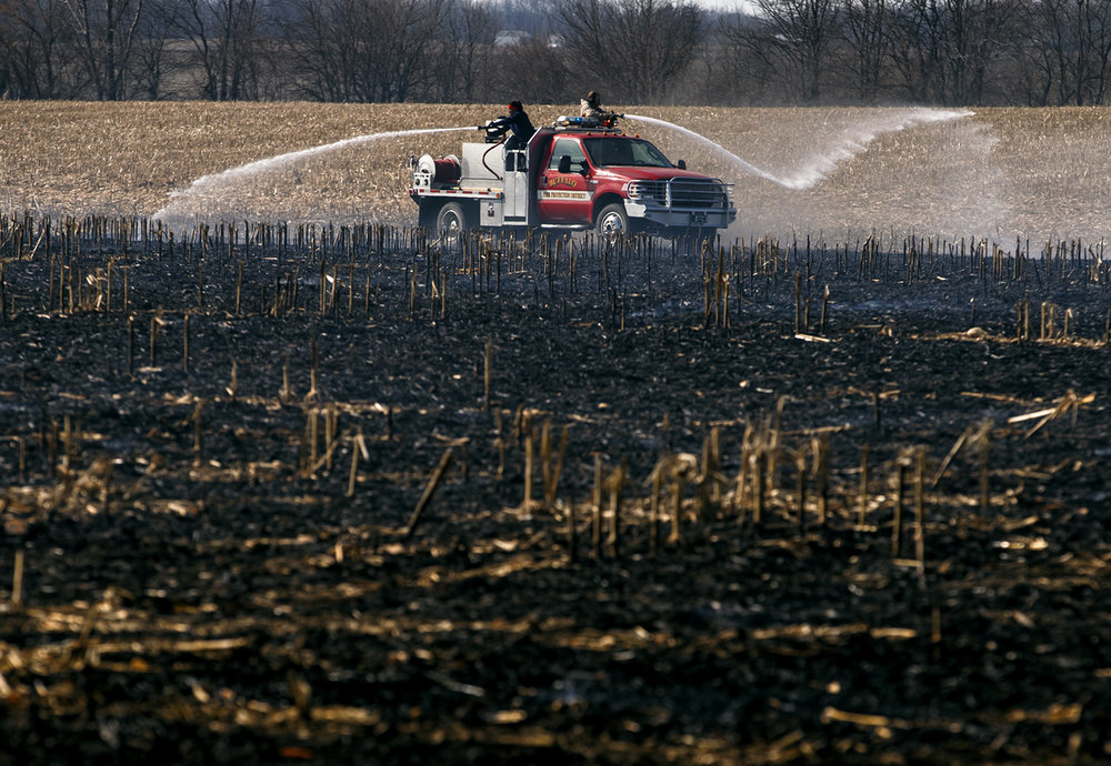 A brush truck from the Buffalo Fire Protection District works the edges of field fire near the intersection of Matthews Road & Water Tower Road, Thursday, Feb. 16, 2017, southwest of Dawson, Ill. The dry remains of corn stalks and high winds pushed the fire through the field as departments from Buffalo, Riverton, Mechanicsburg and Dawson responded to the fire. [Justin L. Fowler/The State Journal-Register]