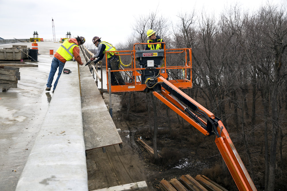 Pete McGlasson, left, his son, Matt McGlasson, and Mandy Price dismantle a safety walkway on a finished portion of the barrier along the west approach to the new $75.1 million bridge that will carry Illinois 104 over the Illinois River at Meredosia Friday, Feb. 10, 2017. The three work for Halverson Construction Co. Inc. of Springfield, the general contractor. The structure is north of the old bridge, which opened in 1936 and will eventually be demolished. [Rich Saal/The State Journal-Register]