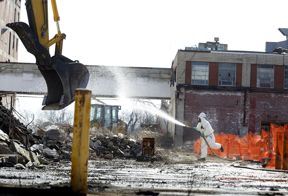 A U.S. Environmental Protection Agency worker dampens a pile of debris Tuesday, Feb. 13, 2017 that is being cleared from the former Pillsbury Mills site on the city's northeast side. Asbestos removal began last week and is expected to take six months and cost $1.8 million. [Rich Saal/The State Journal-Register]