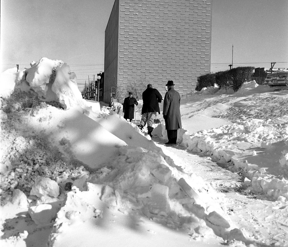 Springfield received 14.4 inches of snow on Feb. 24 and 25, 1964. Workers clear snow from sidewalks along First Street near the Statehouse Inn. File/The State Journal-Register