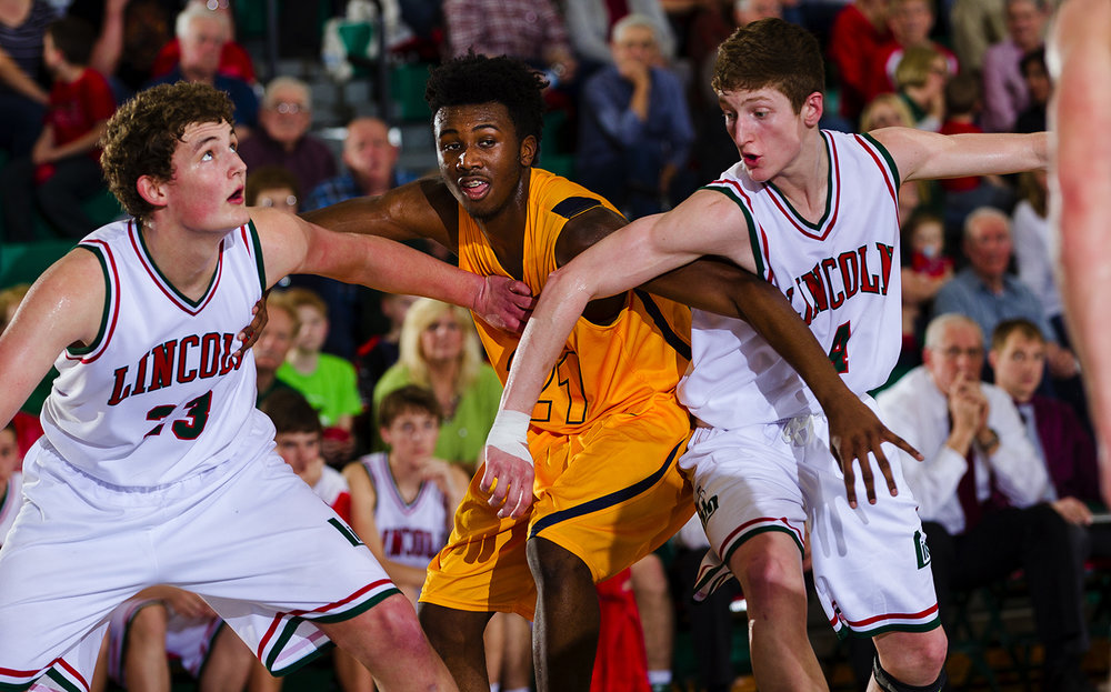 Lincoln's Drew Bacon, left, and Bryson Kirby box out Southeast's Anthony Fairlee at Lincoln High School February 24, 2017. [Ted Schurter/The State Journal-Register]