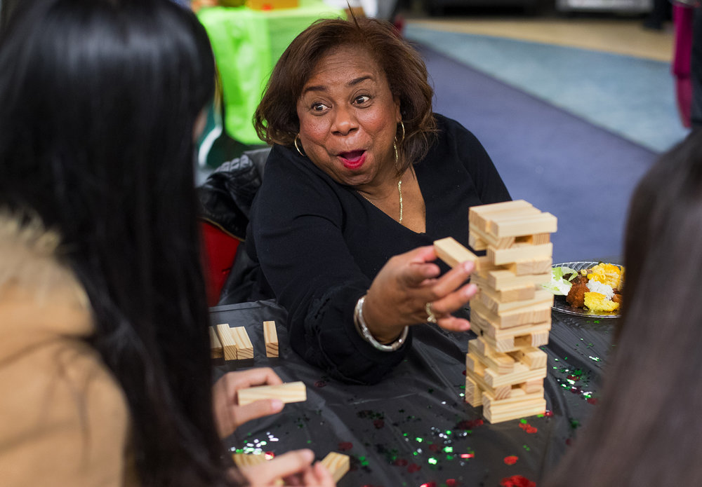 Gertha Lusby reacts as she successfully removes a block during a game of Jenga with with University of Illinois Springfield student Zilin Nong during The Soul Food Festival in the Public Affairs Center on campus Sunday, Feb. 19, 2017. The Black History Month event featured soul food, games, poetry, dance, singing and stepping. [Ted Schurter/The State Journal-Register]