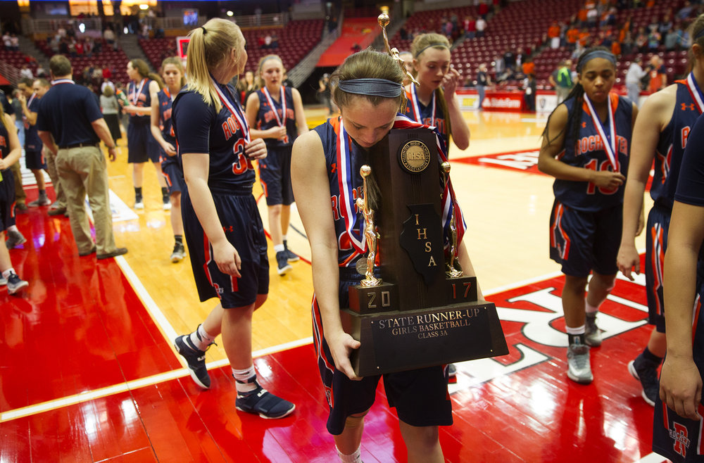 Rochester's Aubrey Magro carries the State Runner-Up trophy off the court after the Rockets lost to Morton during the 2017 IHSA Girls Basketball Class 3A championship game at Redbird Arena Saturday, March 3, 2017. [Ted Schurter/The State Journal-Register]