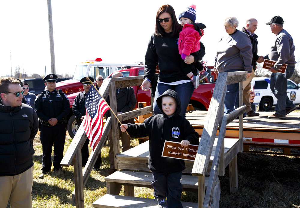 Dani Fitzgerald, widow of Officer Scot Fitzgerald, with her daughter Fynlee, 1 and son, Colton, 5, step down from a platform after a ceremony renaming a portion of Illinois 267 in Morgan County after her husband Friday, March 3, 2017. Scot Fitzgerald was a police officer with the village of South Jacksonville and a Morgan County sheriff's deputy when he was killed in an automobile accident one year ago while responding to a call on the highway. [Rich Saal/The State Journal-Register