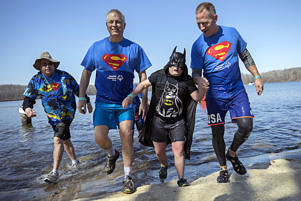 From left, Pat Clausen, Jeff Koch, Special Olympics athlete Nick Sunder and Rich Johnson emerge from Lake Springfield during the 18th annual Law Enforcement Torch Run Polar Plunge to benefit Special Olympics at the Chatham Knights of Columbus Saturday March 4, 2017 [Photo by Jason Johnson]