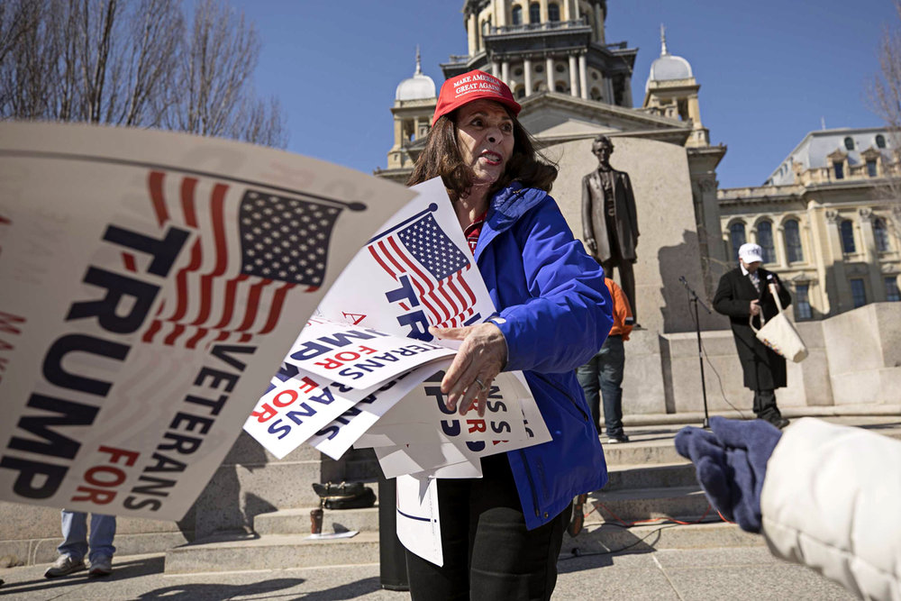 Republican National Committee member and co-chair of Trump for Illinois, Demetria Demonte, hands out Trump posters before March 4 Trump, a nationwide rally in support of the President, gathered on the east steps of the capitol Saturday March 4, 2017 [Photo by Jason Johnson]