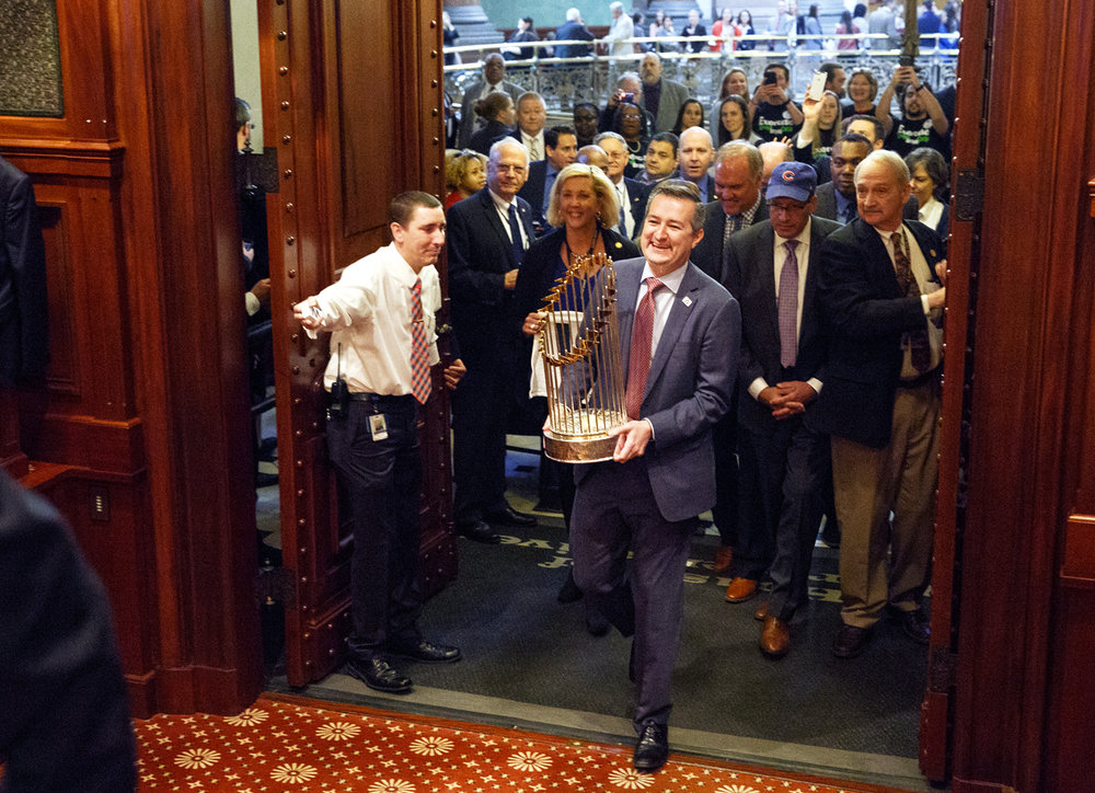 Chicago Cubs Chairman Tom Ricketts carries the Cubs' World Series trophy into the House chamber March 8, 2017 at the Capitol in Springfield, Ill. The World Champion Chicago Cubs were honored during a joint session of the General Assembly. [Rich Saal/The State Journal-Register]