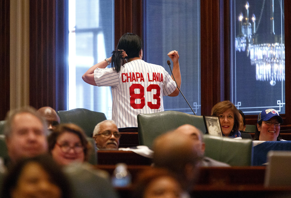 Rep. Linda Chapa LaVia, D-Aurora, shows off her Chicago Cubs jersey during a ceremony to honor the World Champion Cubs in a joint session of the General Assembly at the Capitol Wednesday, March 8, 2017. [Rich Saal/The State Journal-Register]