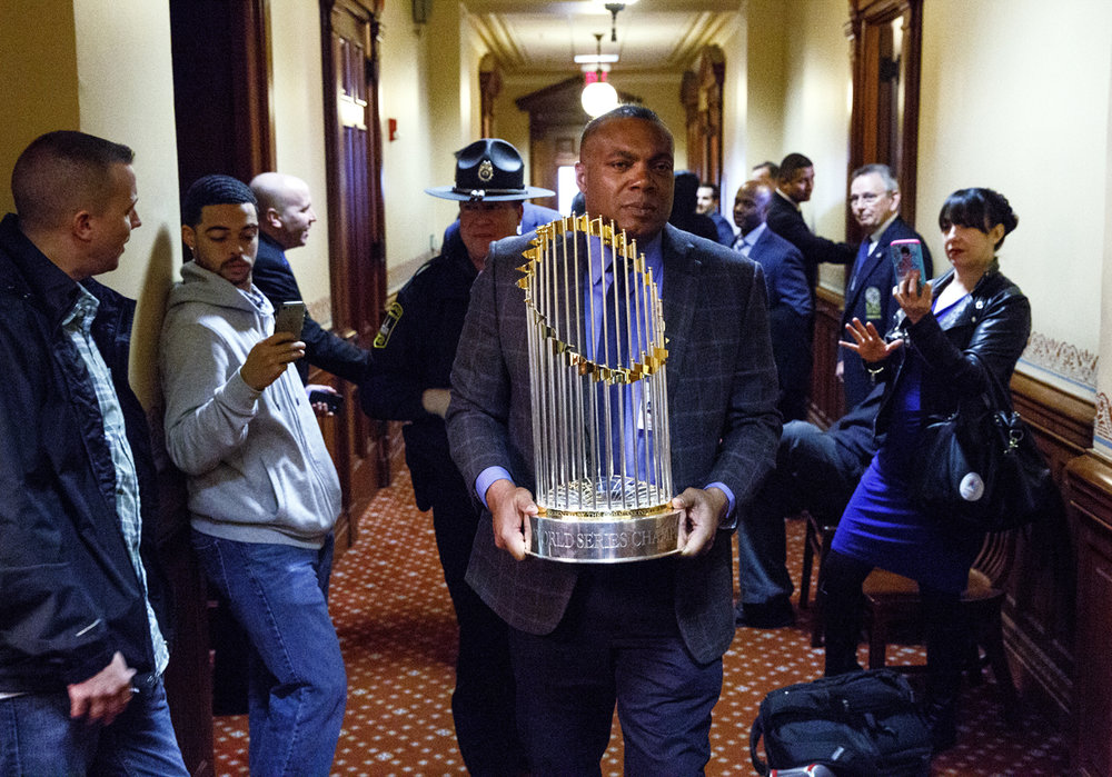 Julius Farrall, protective services manager for the Chicago Cubs, carries the Cubs' World Series trophy from Senate President John Cullerton's office to the House chamber where it was displayed during a joint session of the General Assembly Wednesday, March 8, 2017 at the Capitol. The World Champion Cubs were honored during the special session. [Rich Saal/The State Journal-Register]