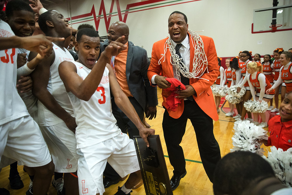 Lanphier head coach Blake Turner and the Lions celebrate their 75-60 win against Mt. Zion during the Class 3A Sectional final in Effingham Friday, March 10, 2017. [Ted Schurter/The State Journal-Register]