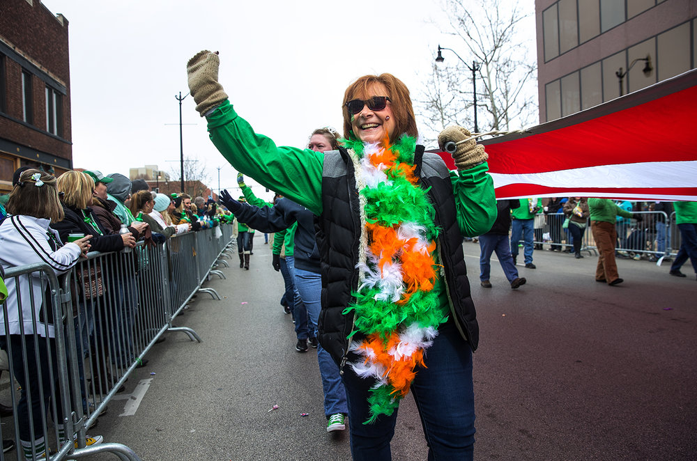 Diane Holler waves to the crowd as she helps carry a United States flag during the St. Patrick's Day Parade Saturday, March 11, 2017. [Ted Schurter/The State Journal-Register]