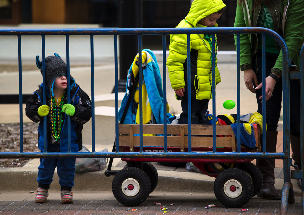 Maddie Brooks, left, peers through the barricades as she watches the St. Patrick's Day Parade with her brother Will Saturday, March 11, 2017. [Ted Schurter/The State Journal-Register]