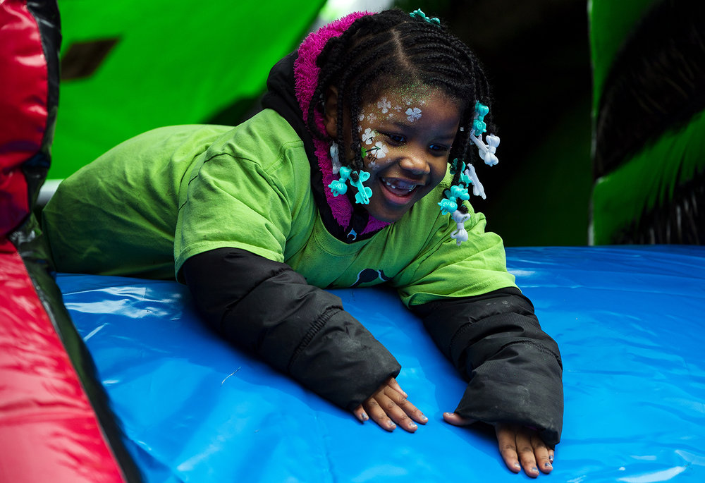 Ashlee Britt slides down an inflatable slide in the children's area at the Old State Capitol after the St. Patrick's Day Parade Saturday, March 11, 2017. [Ted Schurter/The State Journal-Register]