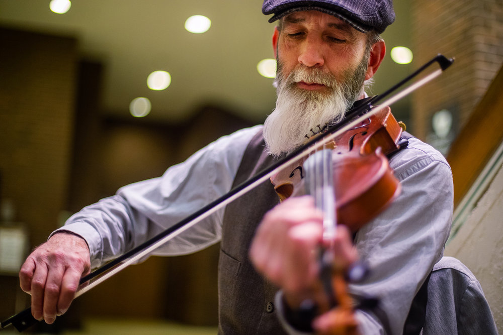 William Wilkie plays a fiddle in the atrium of the Lincoln Library to mark Irish American Heritage Month Thursday, March 9, 2017. Wilkie, a member of the Irish American fusion band Skibereen, performed solo on the fiddle and banjo for patrons. The full band will perform a variety of local venues this weekend. [Ted Schurter/The State Journal-Register]