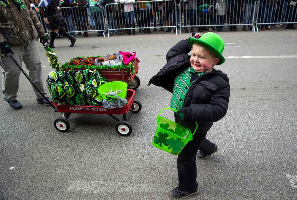 Marcin Moody throws a handful of candy to the crowd during the St. Patrick's Day Parade Saturday, March 11, 2017. Moody was marching with the  St. Andrew's Society of Central Illinois. [Ted Schurter/The State Journal-Register]