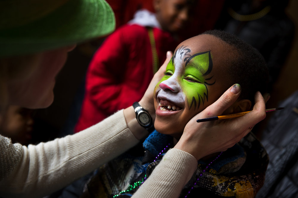 Zyaire Readus smiles at Andrea Murray as she paints his face in a children's area at the Old State Capitol after the St. Patrick's Day Parade Saturday, March 11, 2017. The new area featured inflatable slides, dancing, balloons and music. [Ted Schurter/The State Journal-Register]
