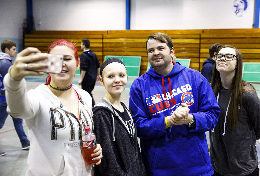Sporting a new, beardless look--some said it made him look younger-- Auburn High School principal Nathan Essex poses for a picture with students Courtney Werries, left, Taylor Califar and Makayla Kleiboeke at the school Friday, March 10, 2017. Essex made good on a promise to get rid of his full beard of 20 years if more than $1000 was raised for Jeff Smith, a biology teacher at the school, and his wife Sarah, who is battling cancer. According to Essex, they were expecting to well exceed that number, with the funds helping the Smiths with travel and other costs related to her treatment in St. Louis. [Rich Saal/The State Journal-Register]