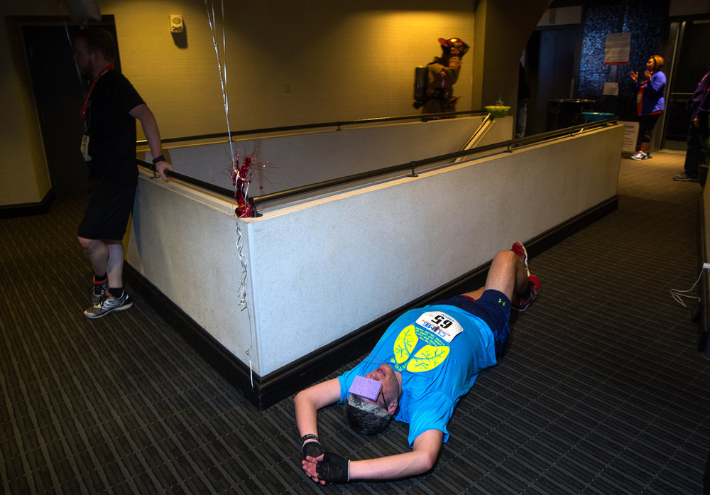 David Garcia of Los Angeles, CA, rests on the ground with a damp sponge on his forehead after completing his eighth trip up the 32 flights of stairs at the Wyndham Springfield City Centre during the American Lung Association's Fight For Air fundraiser Sunday, March 12, 2017. [Ted Schurter/The State Journal-Register]