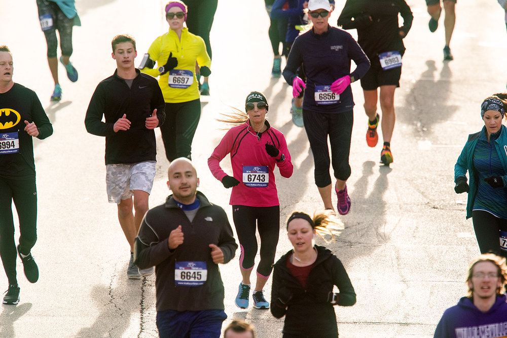 Jennifer Frank, center, joins other runners as they make their way down Capitol Avenue during the Lincoln Presidential Half Marathon in Springfield Saturday, April 1, 2017. [Ted Schurter/The State Journal-Register]
