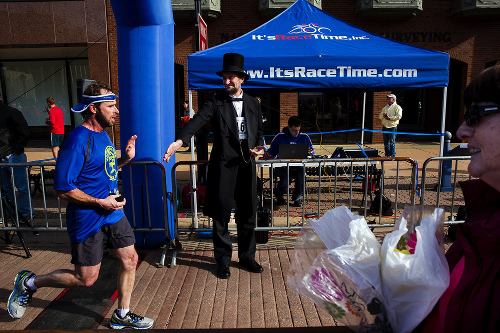 Abraham Lincoln presenter Michael Krebs greets a runner as he crosses the finish line during the Lincoln Presidential Half Marathon in Springfield Saturday, April 1, 2017. [Ted Schurter/The State Journal-Register]