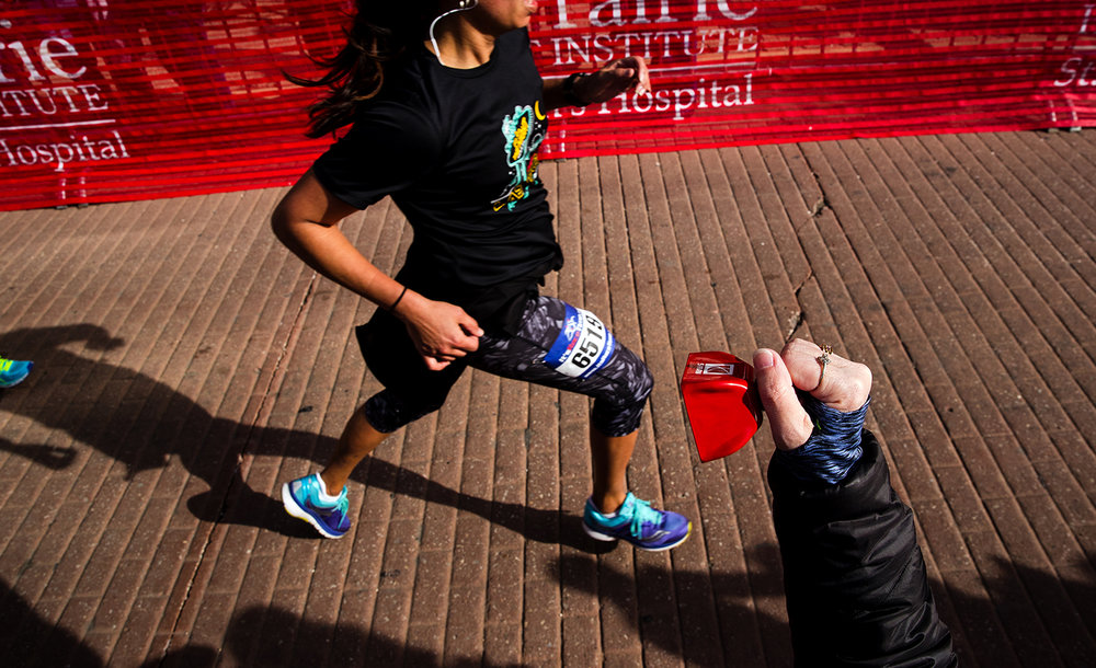 Race marshall Jeanne Harvill encourages runners with a bell as they run down the chute to the finish line at the Lincoln Presidential Half Marathon in Springfield Saturday, April 1, 2017. [Ted Schurter/The State Journal-Register]