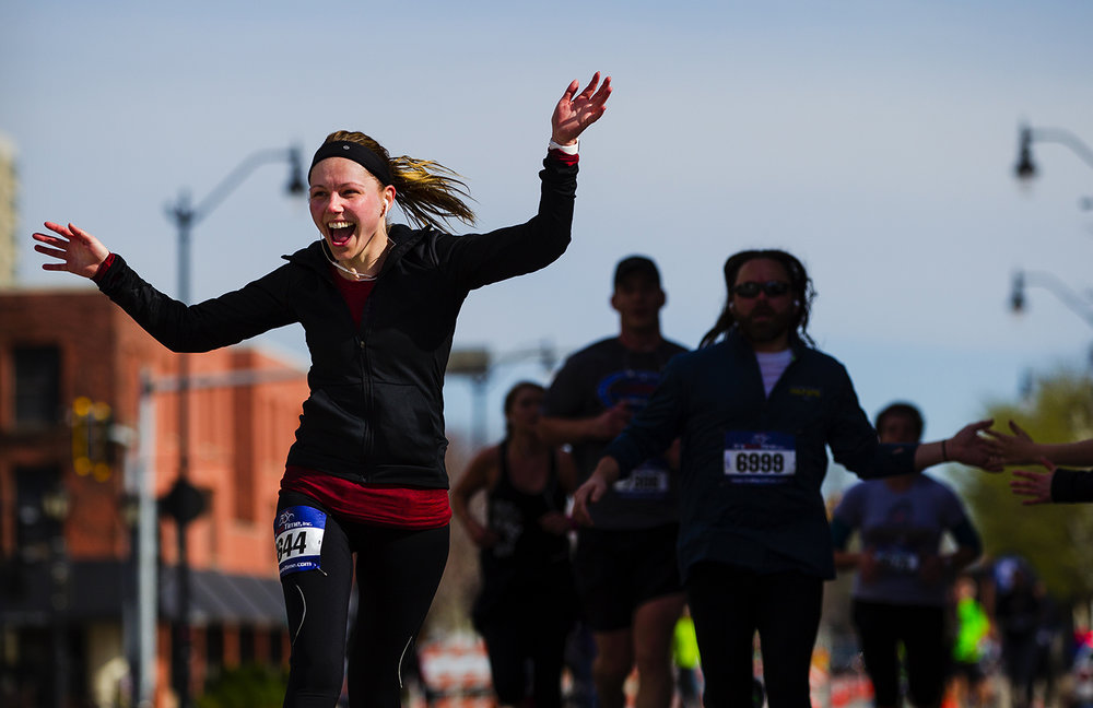 Allison Diliberto waves to the crowd as she nears the finish line at the Lincoln Presidential Half Marathon in Springfield Saturday, April 1, 2017. [Ted Schurter/The State Journal-Register]