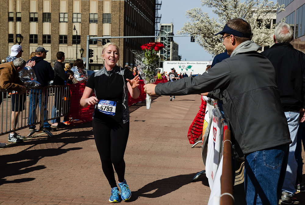 Mike Griffin surprises his daughter Kimber with a bouquet of red roses as she nears the finish line during the Lincoln Presidential Half Marathon in Springfield Saturday, April 1, 2017. [Ted Schurter/The State Journal-Register]