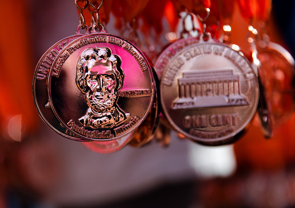 Medals resembling giant pennies sparkle as they await their new owners during the Lincoln Presidential Half Marathon in Springfield Saturday, April 1, 2017. [Ted Schurter/The State Journal-Register]