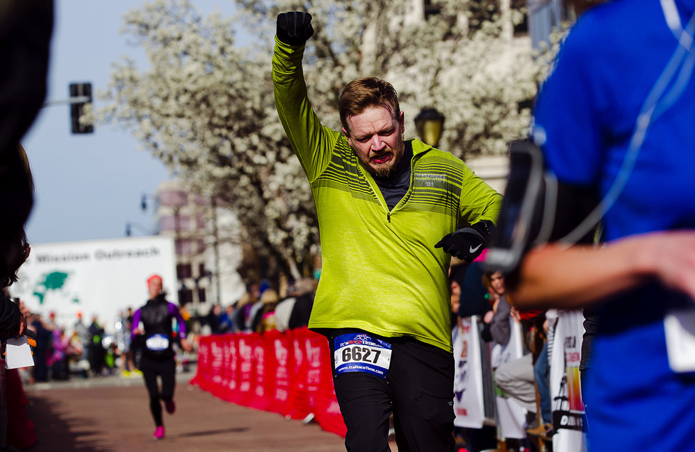 Tadd Davis celebrates as he crosses the finish line in 1 hour 46 minutes and 58.8 seconds during the Lincoln Presidential Half Marathon in Springfield Saturday, April 1, 2017. Davis lost his house in a fire while training for the event and said the local running community supported him through the ordeal. [Ted Schurter/The State Journal-Register]