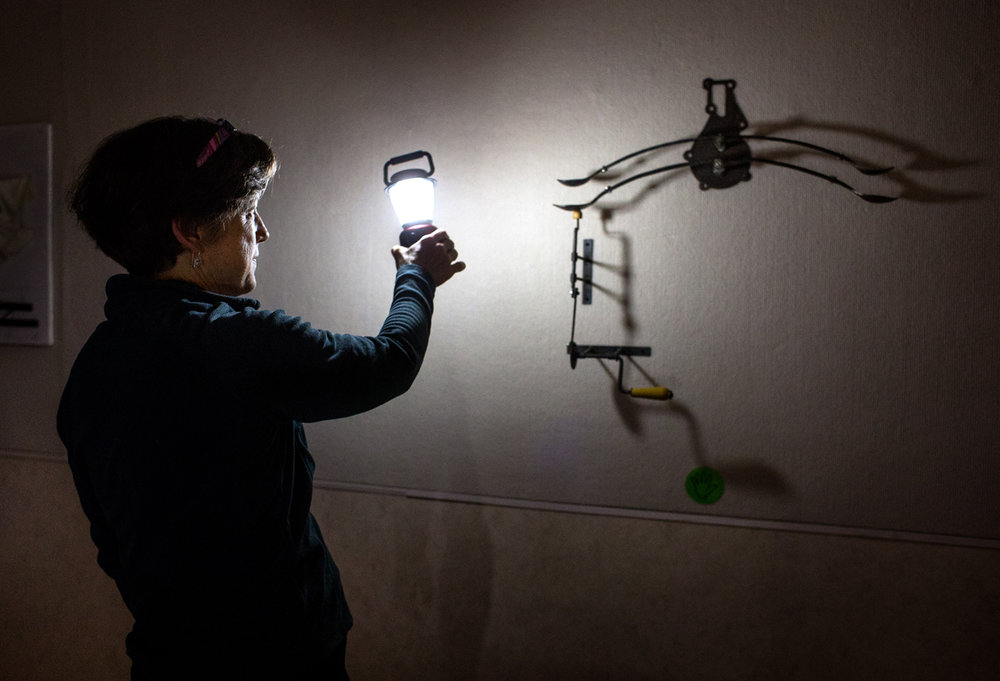 "Springfield Art Association Executive Director Betsy Dollar illuminates Lex Archibald's piece ""Spooning"" during the Lantern Walk at the Springfield Art Association Collective at the Hoogland Center for the Arts Thursday, March 30, 2017. Lights were dimmed for the event and visitors received a lantern to explore the gallery while listening to the poetry of Emma Wilson and Jeff Williams and soundscape musician Timothy Donavan Russell.  [Ted Schurter/The State Journal-Register]"