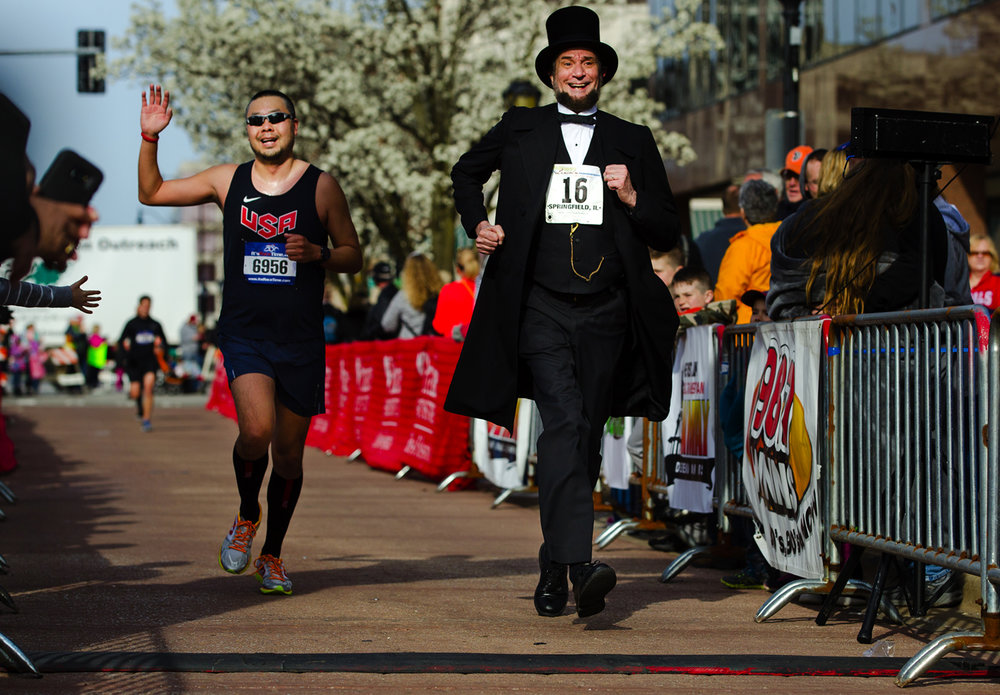 Abraham Lincoln presenter Michael Krebs runs with Peter Kim as he approaches the finish line at the Lincoln Presidential Half Marathon in Springfield Saturday, April 1, 2017. [Ted Schurter/The State Journal-Register]