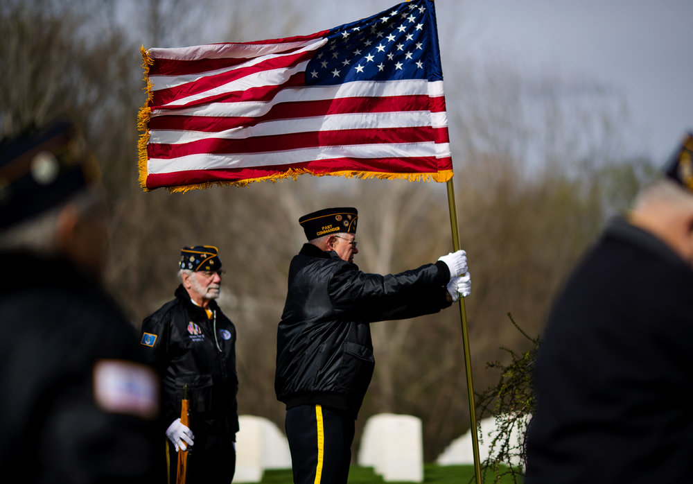 Mike Palazzolo with the Italian American War Veterans Color Guard uses two hands to keep the United States flag upright as it is buffeted by strong winds during a wreath laying commemoration ceremony to honor the 100 year anniversary of the United States entering World War I at Camp Butler National Cemetery Thursday, April 6, 2017. [Ted Schurter/The State Journal-Register]