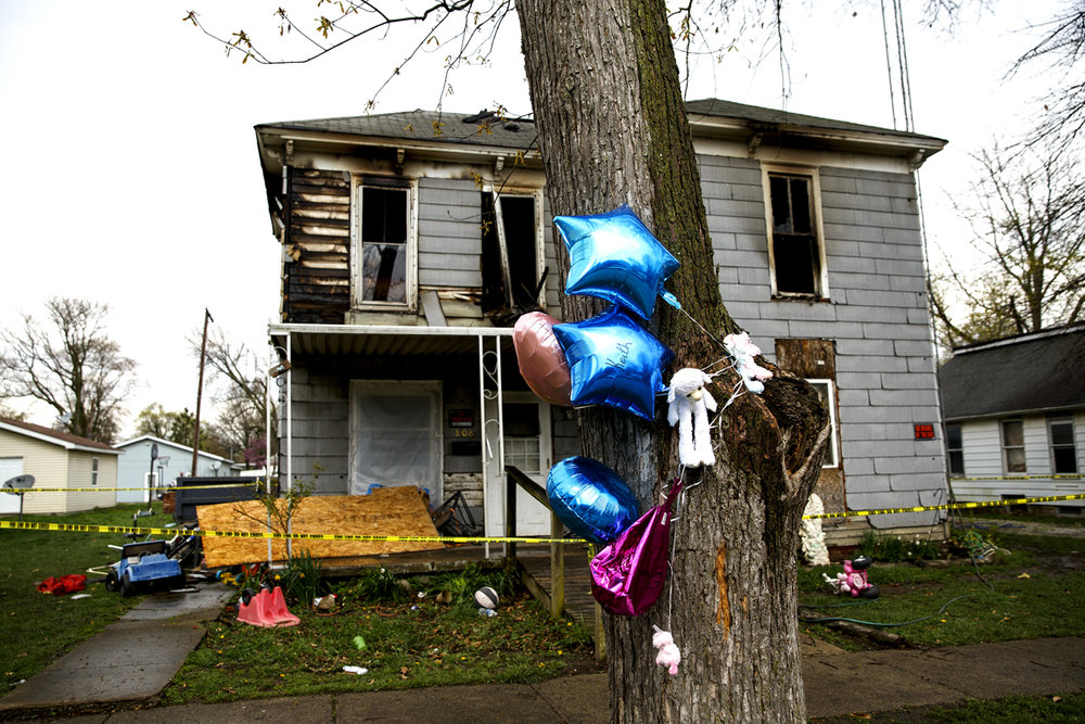 Balloons with the names of Ellaina Graves Emerson, 2, and her infant brother, Keith Emerson, are tied to a tree Monday, April 3, 2017 where the children died of smoke inhalation in a house fire early Sunday. [Rich Saal/The State Journal-Register]