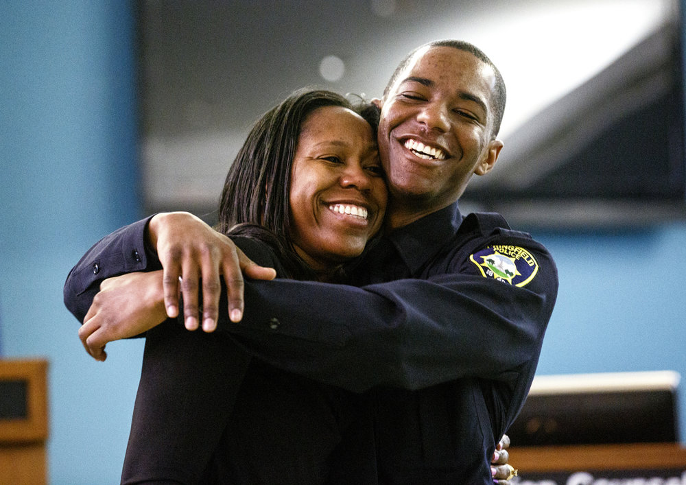 It was a joyful moment for Springfield Police Officer Lamar Moore who hugged his mother Michelle Epps after she pinned his badge on him during the swearing in of seven new Springfield police officers Tuesday, April 4, 2017 in the city council chambers. [Rich Saal/The State Journal-Register]