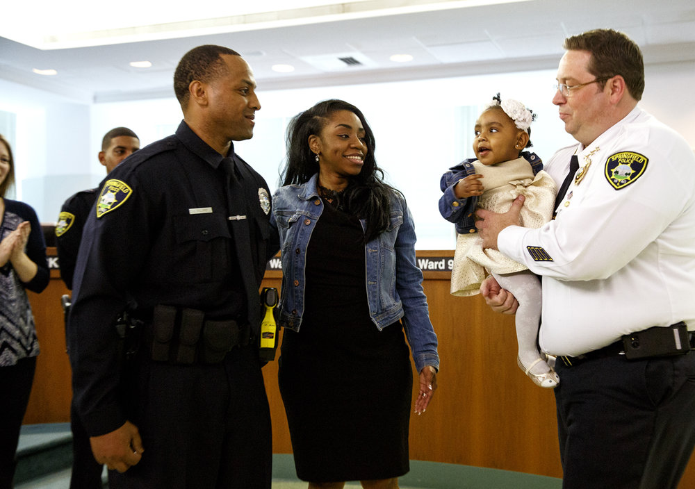 Springfield Police Chief Kenny Winslow lent a hand holding Lauryn Williams, 14 months, when her mother Arlicia pinned a badge on her husband Lawrence during the swearing in of seven new Springfield police officers Tuesday, April 4, 2017 in the City Council chambers. [Rich Saal/The State Journal-Register]