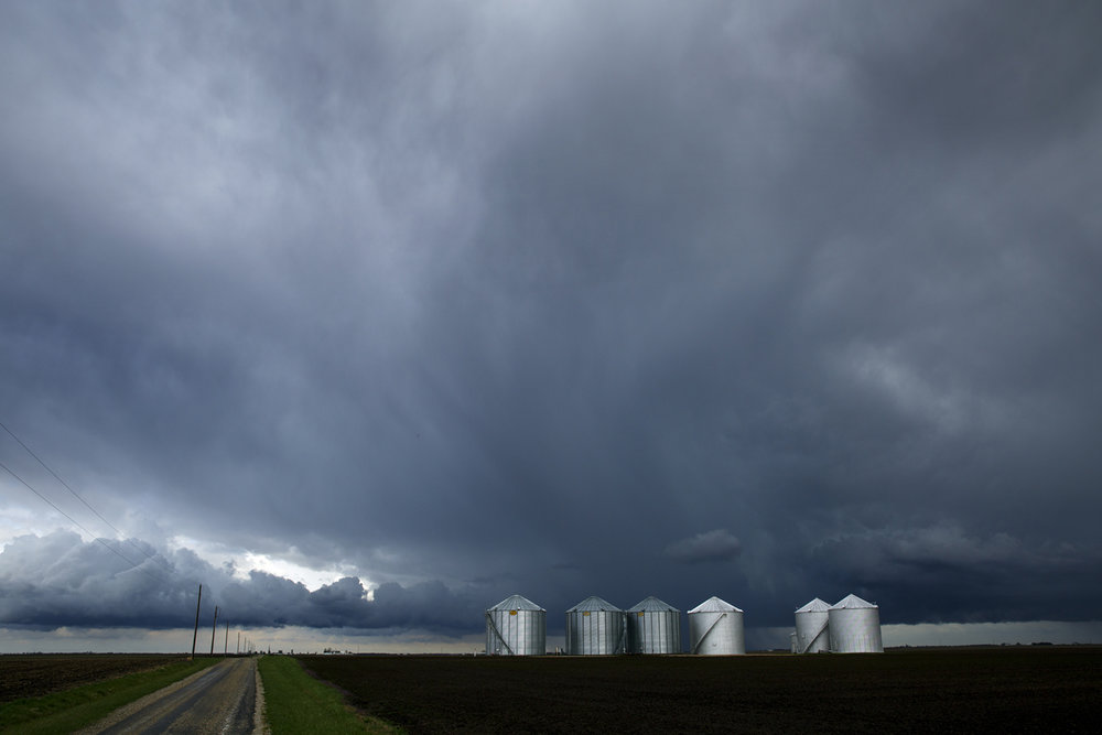 Grain bins stand out against a sky darkened by thunderstorms moving through Christian County Monday, April 4, 2017. [Rich Saal/The State Journal-Register]