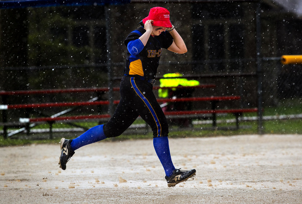 Tri-City's Aubrey Hunt holds onto her hat as she dashes through the rain to retrieve second base after the Tornadoes game against Williamsville was called off due to the weather Monday, April 10, 2017. [Ted Schurter/The State Journal-Register]